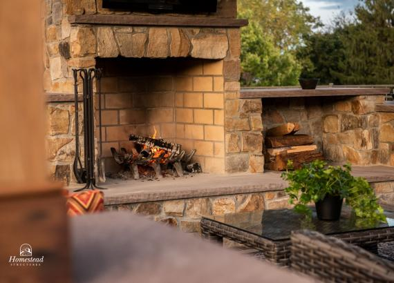 Stone fireplace and wood storage in Timber Frame Pavilion